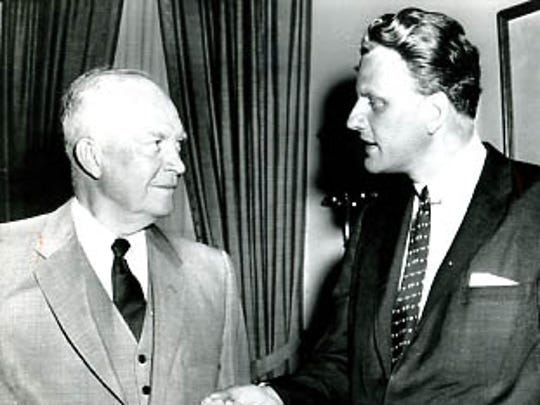 Evangelist Billy Graham talks with President Dwight D. Eisenhower during a call at the White House in May 1957.