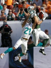 Jets wide receiver Eric Decker catches a pass as Miami Dolphins cornerback Brent Grimes defends in the second half Sunday.