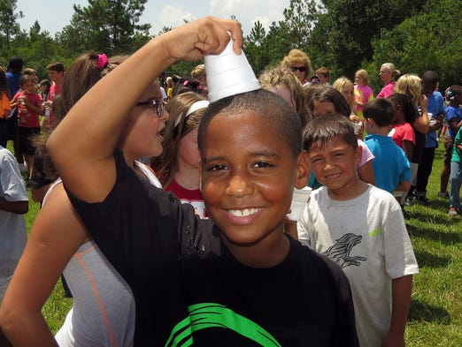 It was so hot outside Friday afternoon Clayton Peoples, 8, a third grader at Blue Angels Elementary couldn't resist pushing a cup full of ice against his head to cool off during the ALS bucket challenge undertaken by the students and staff of the school Friday afternoon.  Students poured cups of ice over their heads as part of the challenge.