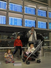 Amy Zampi, 34, Ann Arbor, and her children, from left,  Emma, 3, Ben, 5, and Maggie, 1,  wait for their flight  to Greenville, S.C., on the busiest travel day of the year,  at the McNamara Terminal in Detroit Metropolitan Airport in Romulus, Michigan on November 26, 2014.  Charles V. Tines, The Detroit News.