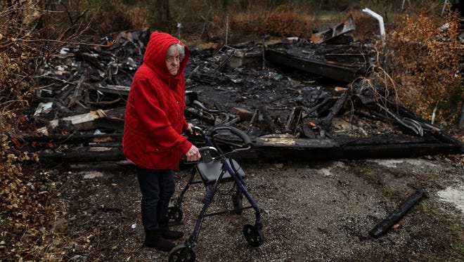 """Patricia Shipman, 72, examines the burned remains of her former neighbors home in the Pleasant Ridge neighborhood of Charlestown, Indiana. Shipman, who uses a walker to get around, was awoke at 6 a.m. by a passerby informing her of the fire. """"The flames were 30-40 feet high,"""" Shipman said. """"I was scared my house would burn down. The flames were coming over onto my roof. Shipman's home was spared, but she and other elderly residents living beside vacant homes are now living in fear of fires. Since renters have been pushed out of homes, some vacant homes have caught fire for uncertain reasons, but residents blame homeless squatters. Dec. 5, 2017"""