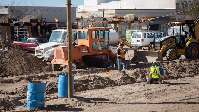 Construction workers on the downtown plaza site Friday. According to city officials, infrastructure work underneath the plaza is now finished and a July completion date for the project is still on target.