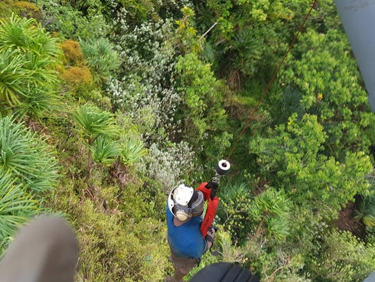 A distressed hiker is hoisted up to an MH-60S helicopter