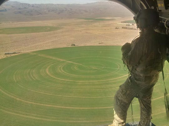 A crew chief from Task Force Iron Dragon looks out on Death Valley, Calif., from a Chinook during the recent National Training Center rotation.