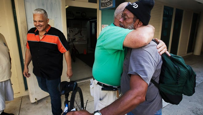 Harry Figueroa get the obligatory hug from Working Hands Ministry director Ken NIes after receiving a bike on Wednesday. Figueroa is living out of his car. On the left is Gedalias Donato, an employee at Abuse Counseling Treatment. The needy can receive a free blke at the ministry if they volunteer 8 hours at a non-profit or religious entity.