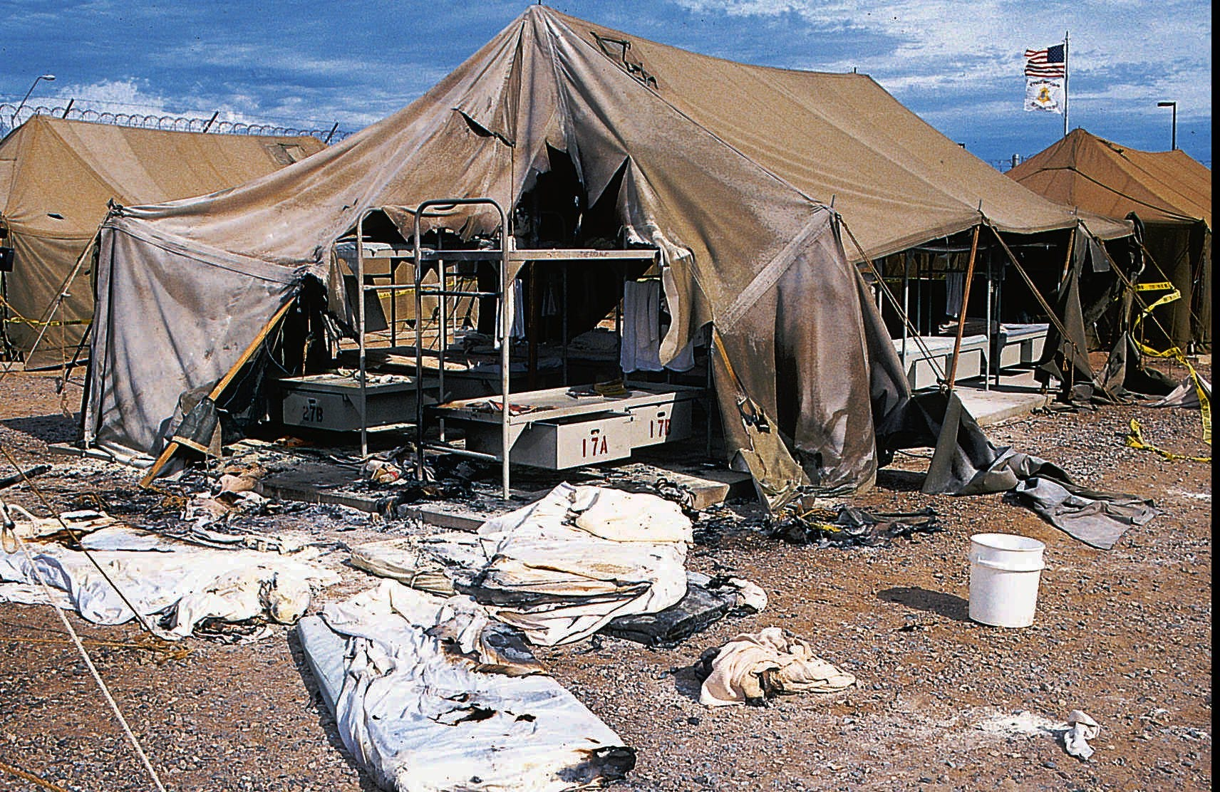 Oct. 1994 Charred mattresses are spread out in front & Tent City infamous home of inmates who wear pink underwear and ...