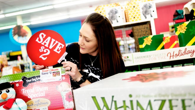 Pet Supermarket district manager Caitlin Greenwell finishes setting up a display of holiday sale items at their Kingston Pike location in Knoxville, Tennessee on Wednesday, December 13, 2017. Pet Supermarket is offering holiday deals on everything from animal toys to dog food.