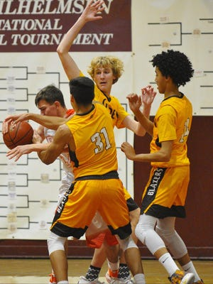 Golden West's R. J Ortega (31), Hunter Bayne and Shemar Smith scramble for the rebound against Porterville in Thursday's semifinal game at the 66th Polly Wilhelmsen Invitational at Mt Whitney High School.