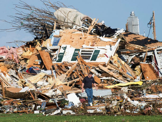 A man walks through a storm-damaged home in Gifford, Ill.