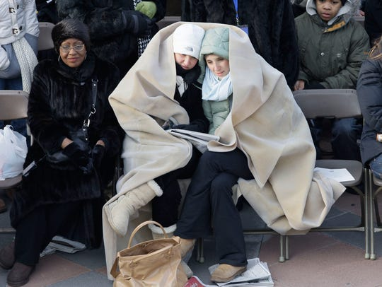 Inauguration attendees try to stay stay warm as they