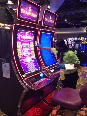 """Rosauri Birriel, a member of the Finger Lakes Gaming & Racetrack's """"Clean Team,"""" makes sure a gaming machine is clean and safe for customers who returned to the Farmington facility Wednesday."""