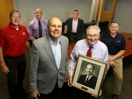 Three generations of ownership of Isaac Heating and Air Conditioning are represented in this photo, including a portrait of George T. Isaac as founder and Bill and Jim (front, left to right).  Dave, Ken, Ray and Mike Isaac.
