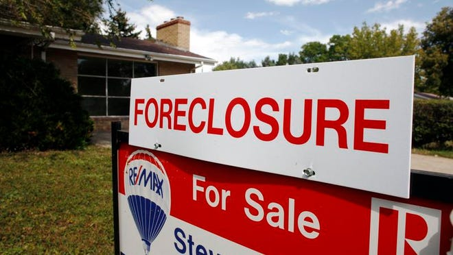 A foreclosure sign stands on top of a sale sign outside an existing home for sale.