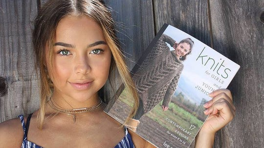 "Lee Gant's granddaughter holds a copy of ""Knits for"