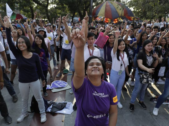 Women activists dance as they mark International Women's Day in Manila, Philippines on Friday, March 8, 2019. The group criticized Philippine President Rodrigo Duterte, opposed martial law in Mindanao and called for equal rights. (AP Photo/Aaron Favila)