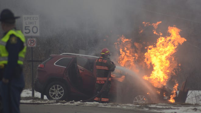 Emmett Township firefighters battle a car fire after the driver lost control and struck a utility pole during a police pursuit.