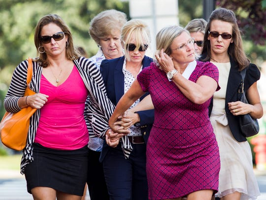 Former Baltimore Ravens cheerleader Molly Shattuck (center) is surrounded by supporters as she walks to the Sussex County Courthouse in Georgetown, Del. on Friday morning.