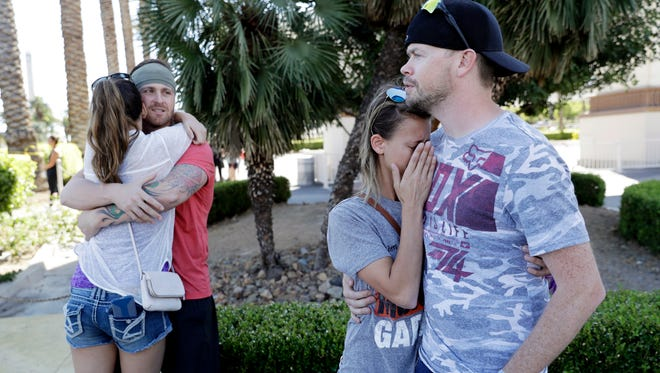 Sean Bean, of Livermore, Calif., hugs his girlfriend, Katie Kavetski, of San Leandro, Calif., left, as Travis Reed, of Mexico, Ind., right, comforts his girlfriend, Anna Travnicek, second from right, on Las Vegas Strip.  All attended the concert where the mass shooting occurred.