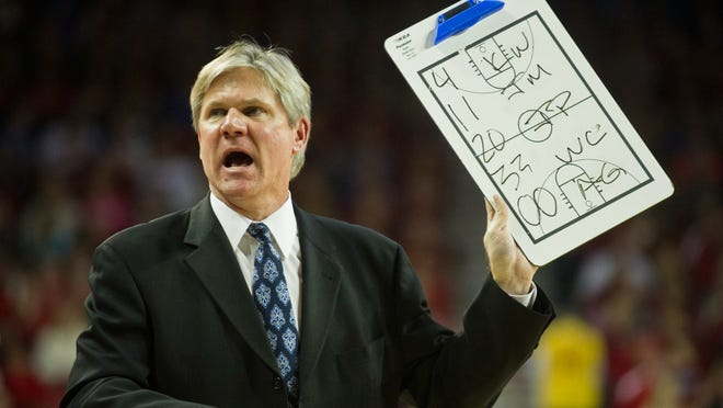 Kentucky Wildcats assistant coach John Robic holds up a clip board during a time out at 2013 game against the Arkansas Razorbacks at Bud Walton Arena.