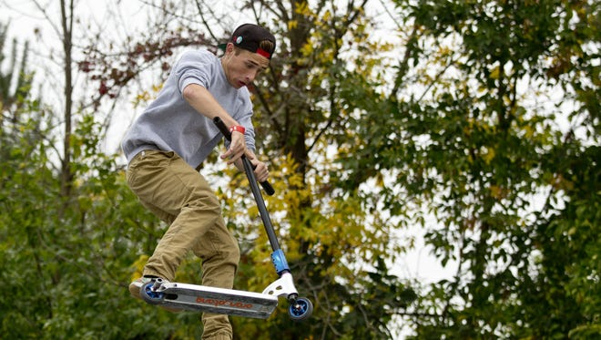 Randy Harwood, of St. Clair, does a trick in the air on his scooter during the 2015 Fall Grind at the St. Clair Skate Park.