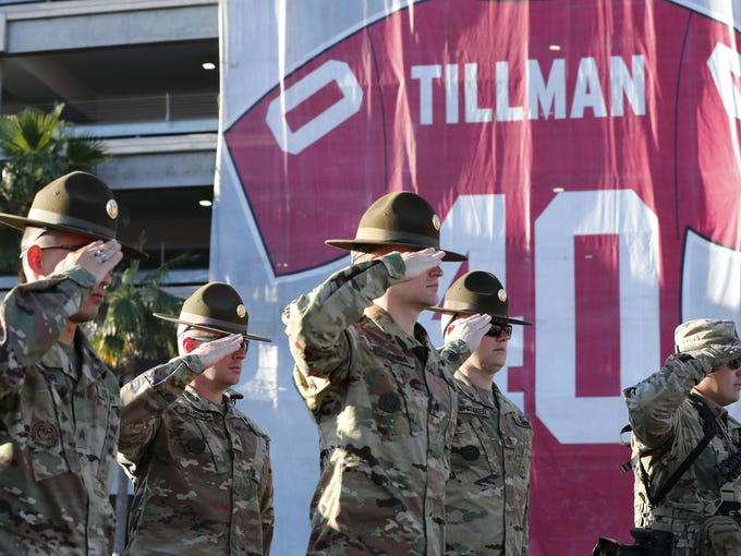 Army reservists salute during the National Anthem during