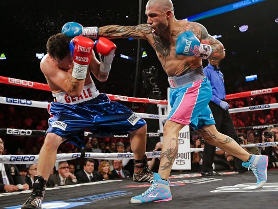 FILE - In this June 6, 2015, file photo, Miguel Cotto, right, of Puerto Rico, punches Daniel Geale, of Australia, during the second round of a boxing match in New York. Cotto is a boxing icon in Puerto Rico. In New York City, too. On Saturday night the most popular boxer of his generation from the Caribbean island that has produced so many champions will finish off his terrific career at Madison Square Garden with a title fight. (AP Photo/Frank Franklin II, File)