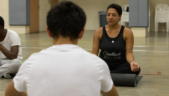 Yoga teacher Ashley Chapa leads a group of juveniles in medication at the end of the Nueces County Juvenile Justice Center's weekly yoga class.