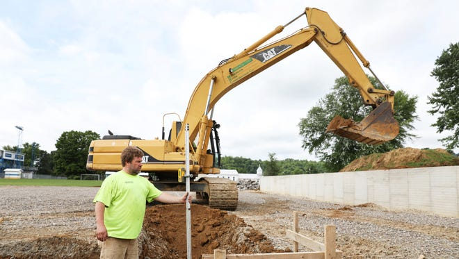 Shane Parsons, owner of Muskingum River Construction, checks the progress of a trench being dug at the site of the new locker rooms at Philo High School's Sam Hatfield Stadium.