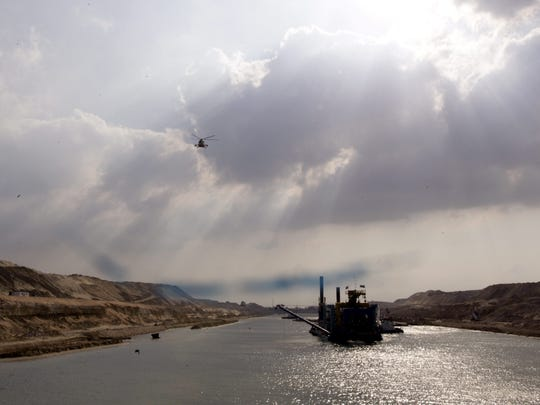 An Egyptian army helicopter flies over a dredgers working