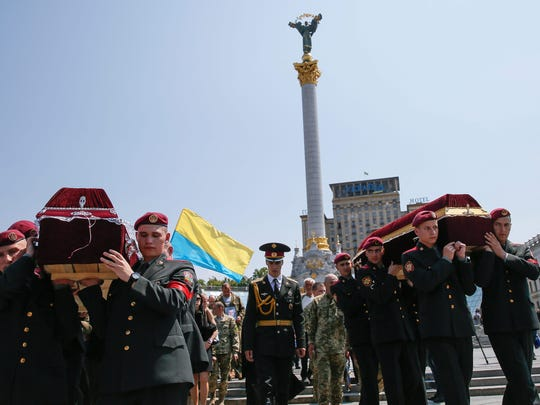 Ukrainian soldiers carry coffins with the bodies of