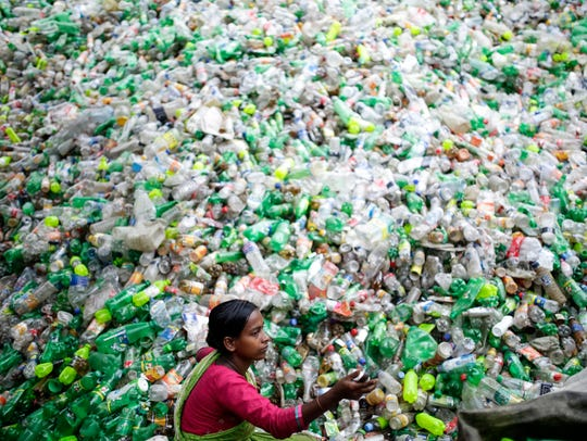 A female laborer sorts through polyethylene terephthalate (PET) bottles in a recycling factory at Mohammadpur in Dhaka, Bangladesh. Recycling plastic bottles has became a growing business over the past couple of years.