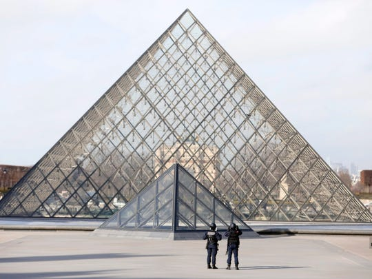 Police officers stand guard near the Pyramid of Le