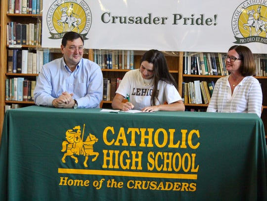 Pensacola Catholic's Lizzy Nowak (center) signs Wednesday