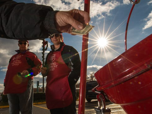 Salvation Army bell ringer volunteers ring their bells watching a donation into a kettle outside a Giant grocery store Nov. 24, 2012, in Clifton, Va.