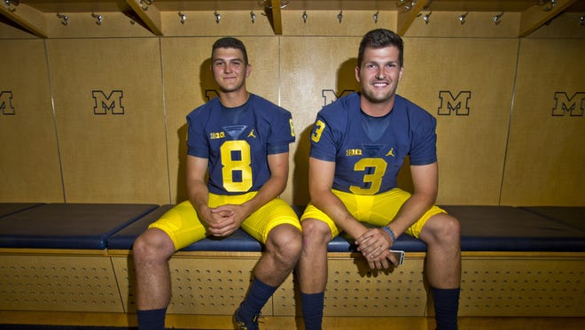 Michigan quarterbacks John O'Korn (8) and Wilton Speight (3) sit for a photo in the locker room during the NCAA college football team's preseason media day at Michigan Stadium in Ann Arbor, Mich., Sunday, Aug. 7, 2016.