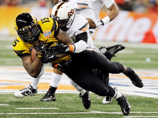FILE - In this Jan. 3, 2014, file photo, Missouri wide receiver Dorial Green-Beckham (15) is tackled by Oklahoma State safety Daytawion Lowe during the second half of the Cotton Bowl NCAA college football game in Arlington, Texas. Green-Beckham has been suspended indefinitely for an unspecified violation of team rules, three months after he and two friends were arrested on suspicion of felony drug distribution. Coach Gary Pinkel announced the suspension Monday, April 7, in a brief news release. (AP Photo/Brandon Wade, File)