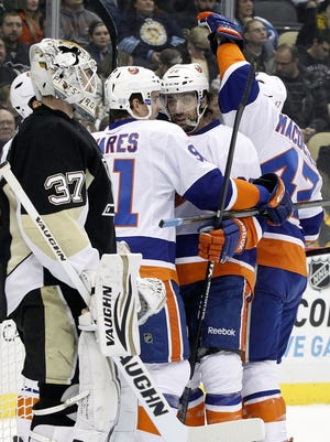 Penguins goalie Jeff Zatkoff (37) can only watch as Matt Moulson, right center, celebrates his first-period goal with the Islanders.