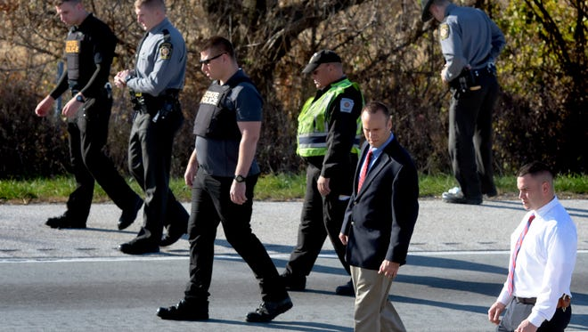 State Police walk along a closed southbound I-83 searching for evidence after a car crashed into a tractor-trailer after the car's driver was apparently fleeing police north of the Emigsville Exit Tuesday, Nov. 15, 2016. The coroner was called to the scene. Bill Kalina photo