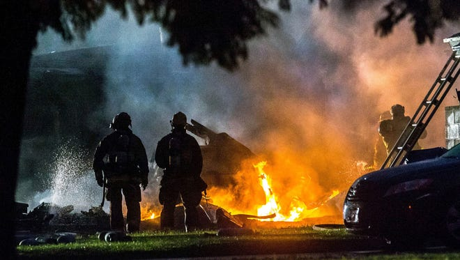 Firefighters put out flames after a plane crashed in Riverside, Calif., Monday, Feb. 27, 2017. The deadly crash injured several when a small plane collided with two homes Monday shortly after taking off from a nearby airport, officials said.