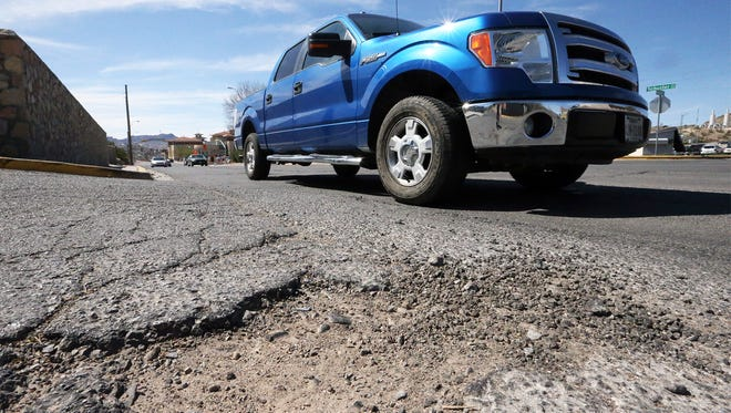 Potholes and cracks along Schuster Avenue at the intersection with Randolph Drive near the UTEP campus are shown in February 2017.