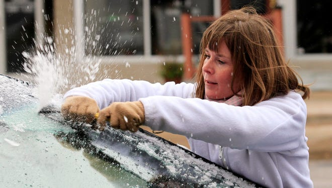 Krystal Wright scrapes ice from her car's windshield Friday, Nov. 27, 2015 in Wichita, Kan. The winter weather left a layer of ice on roads and cars early Friday morning after a heavy rain on Thanksgiving day that set a record with over 2 inches of rain.
