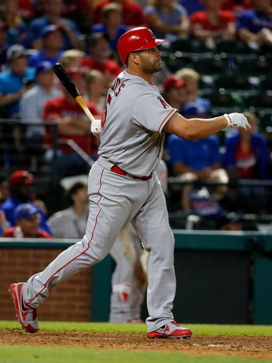 Los Angeles Angels designated hitter Albert Pujols watches his solo home run to left off Texas Rangers reliever Phil Klein during the ninth inning of a baseball game, Saturday, April 30, 2016, in Arlington, Texas. The Rangers won 7-2. (AP Photo/Tony Gutierrez)