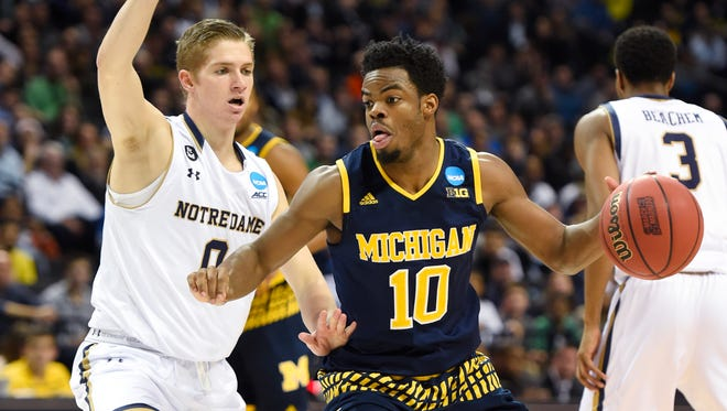 Michigan guard Derrick Walton Jr. controls the ball against Notre Dame guard Rex Pflueger in the second half of U-M's 70-63 loss to Notre Dame in the first round of the NCAA tournament Friday in Brooklyn, N.Y.