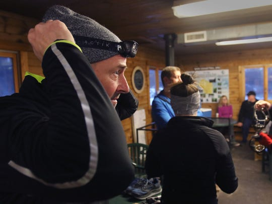 Tom Dircks of Brookfield adjusts a headlamp as eight people gather in a Lapham Peak Unit of the Kettle Moraine State Forest shelter before the start of a Wednesday evening run by the Lapham Peak Trail Runners.