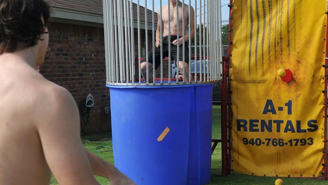 Wichita Falls Wildcat hockey players Kevin Fess (left) and Sami Pharaon test their dunking booth during the 2016 Texoma Gives event. Texoma Gives is an annual 16-hour campaign to gather  support for non-profit organizations.