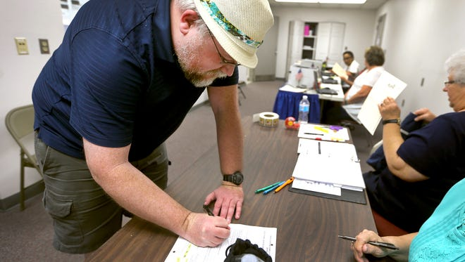 Alex Benjamin signs in to vote at Smyrna Town Hall during the first day of early voting, on Friday July 15, 2016.