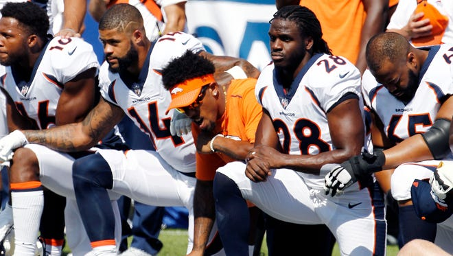 Denver Broncos players, including Jamaal Charles (28) kneel during the national anthem prior to an NFL football game against the Buffalo Bills, Sunday, Sept. 24, 2017, in Orchard Park, N.Y.
