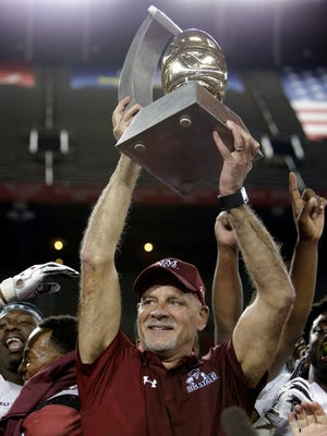New Mexico State head coach Doug Martin lifts the trophy after defeating Utah State in the Arizona Bowl NCAA college football game, Friday, Dec. 29, 2017, in Tucson, Ariz. (AP Photo/Rick Scuteri)