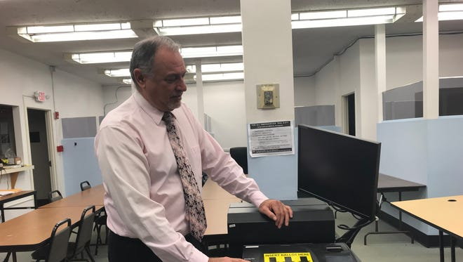 Marco Caviglia, Dutchess County Democratic Elections Commissioner, with one of the county's voting machines.