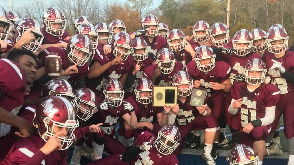 Albertus Magnus' football team celebrates with the plaque after defeating Dobbs Ferry 17-7 in the Section 1 Class C final on Nov. 4, 2017. It was the program's first-ever section title.